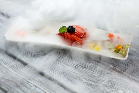 Smoke over plate with dessert. Mint leaf and sliced strawberry. Flan with juicy berries. Dessert from restaurant menu.