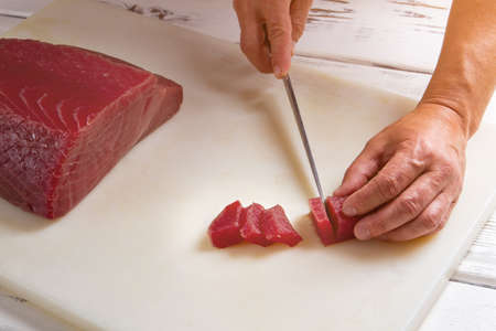 chose: Hand with knife cuts meat. Slices of raw fish meat. Expensive tuna for delicious dish. Chef chose the best fish.