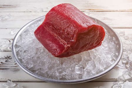 low temperature: Red meat lying on ice. Plate with raw fish meat. Food ingredient of high quality. Product stored at low temperature.