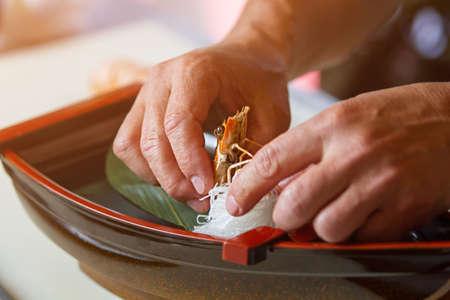 shrimp boat: Mans hands touch cooked shrimp. White noodles and shrimp. Decoration for sushi boat. Japanese cafe chef at work.