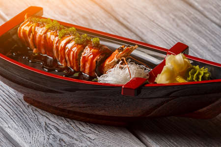 shrimp boat: Sushi boat on wooden background. Cooked shrimp beside sushi rolls. Uramaki rolls with soy sauce. Salty sauce and fresh wasabi.