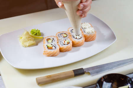 pastry bag: Pastry bag over sushi rolls. Tool puts cream cheese. White plate with uramaki rolls. Last steps in preparing dinner.