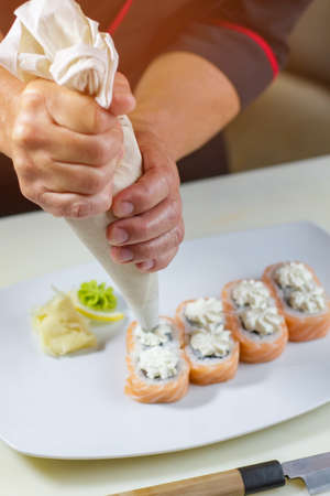 pastry bag: Sushi rolls on plate. Pastry bag in mans hands. Japanese dish with cream cheese. Appetizing uramaki rolls. Stock Photo