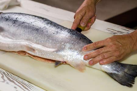 Küchenmesser schneidet rohem Fisch. Man Hand auf rohem Fisch. Küchentisch in Sushi-Bar. Lachsfleisch Rezept erforderlich.
