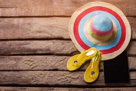 flip flops on the beach: Hat and yellow flip flops. Beach hat and a tablet. Ladys essentials for vacation. Take your time and relax.