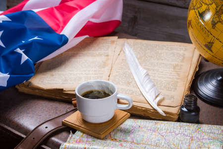 bygone: USA flag near opened book. Coffee cup and map. History of Americas discovery. Tale about the bygone days.
