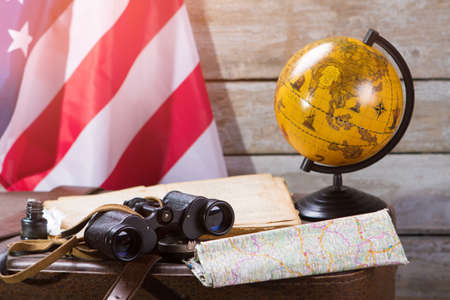 world flag: USA flag behind globe. Map and inkwell with feather. Morning in captains cabin. Voyage along the american coast. Stock Photo