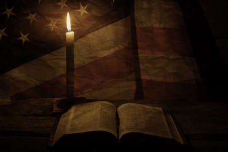 solace: Old USA flag near candle. Open book and burning candle. Faith is a guiding light. We will find solace.