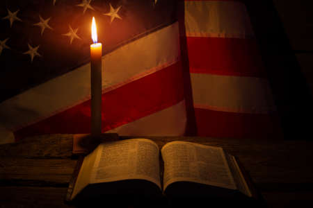 Open book and burning candle. USA flag by candlelight. Bible on old table. Spirituality and solitude. Banque d'images