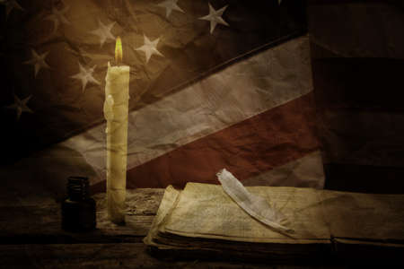 epoch: Book and old US flag. Book and feather near candle. Stories from bygone epoch. History teaches the nation. Stock Photo
