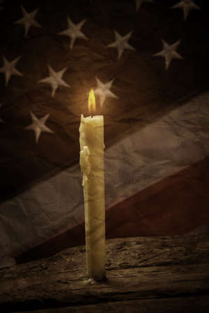 priceless: Candle and old american flag. Burning candle on wooden surface. Light will show the way. Peace is a priceless treasure.