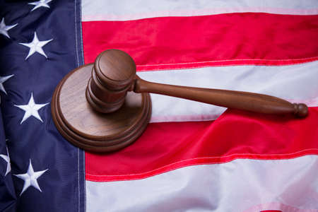 protects: Gavel on USA flag. Brown gavel on american banner. System wont fail. Authority protects law-abiding citizens.