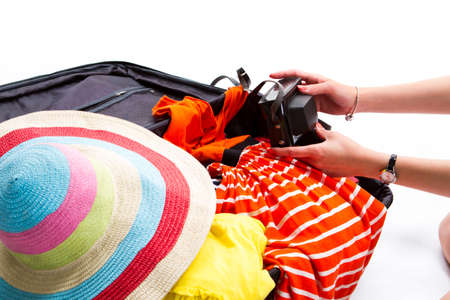 overfilled: Camera case on filled suitcase. Girls hands touch camera case. Dont forget the camera. Bring a photo from journey.