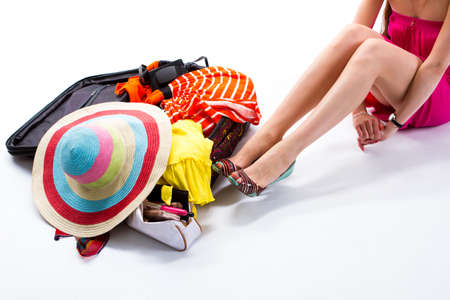 overfilled: Woman sitting beside filled suitcase. Open suitcase with clothes. Preparation for the journey. Take everything you need. Stock Photo