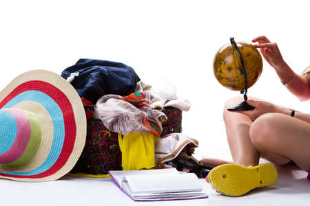 overfilled: Globe in womans hand. Overfilled suitcase and notepad. Lady planning her journey. Which place is best.