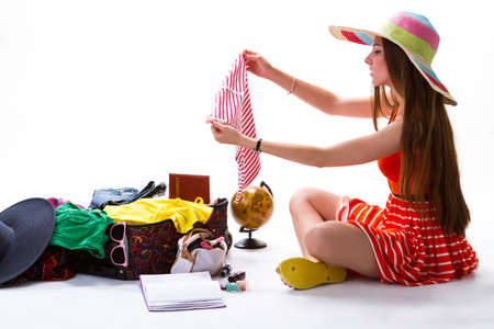 overfilled: Lady in hat beside suitcase. Woman holds striped tank top. Beach clothing for a trip. Always stay stylish.