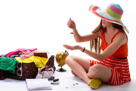 hand in pocket: Girl sits near open suitcase. Coins fall into womans hand. Pocket money for vacation. Manicure and striped beach hat.