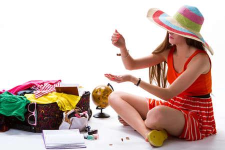 money pocket: La muchacha se sienta cerca de la maleta abierta. Monedas caen en mano de la mujer. El dinero de bolsillo para las vacaciones. Manicura y sombrero de playa a rayas.
