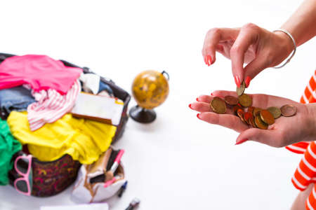 overfilled: Ladys hand takes a coin. Opened bag with clothes. Money saved for a trip. Hands with orange manicure. Stock Photo