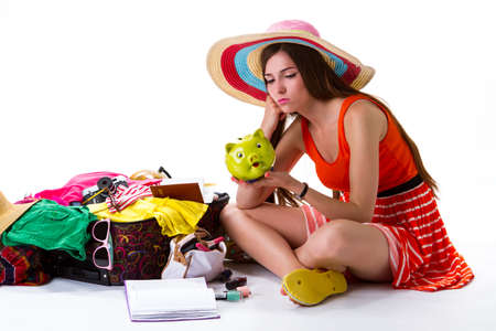overfilled: Girl sits near open suitcase. Woman with green money box. She dreams of better days. Not enough money for vacation. Stock Photo