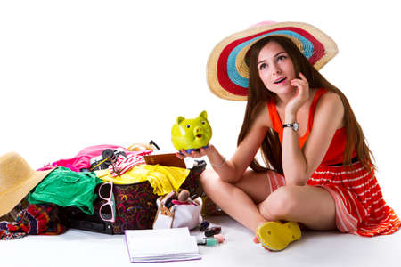 overfilled: Girl beside overfilled suitcase. Woman holds green piggy bank. All savings for the journey. Bright thoughts and good mood. Stock Photo