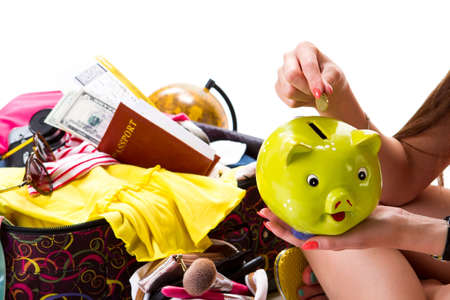 overfilled: Girls hand with piggy bank. Passport on filled suitcase. Savings for next holiday season. Make your dreams come true. Stock Photo