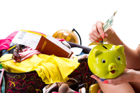 overfilled: Womans hand holds piggy bank. Passport on overfilled suitcase. Travel will cost a lot. Costs for visa and ticket.
