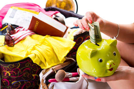 overfilled: Girls hand holds piggy bank. Passport on open suitcase. Expenses for vacation. Dollar bill and money box.