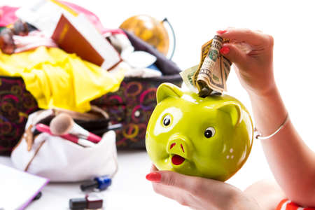 overfilled: Piggy bank on girls hand. Folded dollars and money box. Money needed for the journey. Forget about everyday troubles.