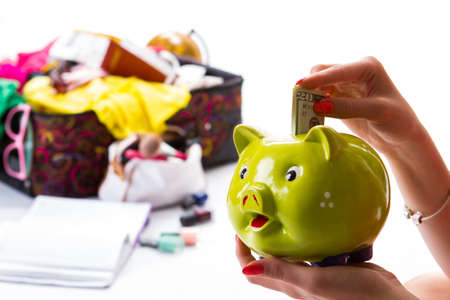 overfilled: Womans hand with piggy bank. Folded dollar bills. Travelling requires expenses. She earned enough money. Stock Photo