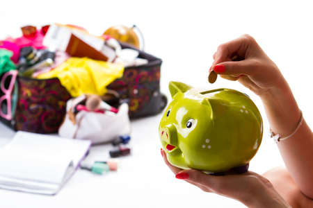overfilled: Ladys hand with piggy bank. Coin and lime money box. The most expensive trip. Make savings for the future.