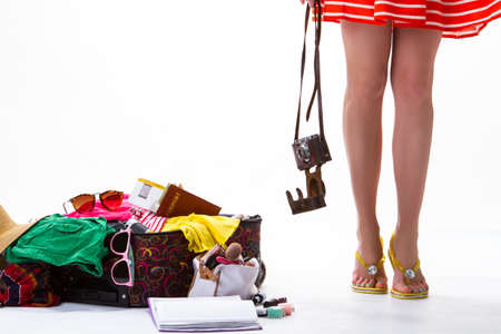 decides: Womans legs and overfilled suitcase. Photo camera in opened case. Young photographer decides to travel. All that you need. Stock Photo