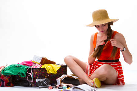 overfilled: Girls sits near overfilled suitcase. Lady with braid wearing hat. Pack your things for vacation. Time for a good rest.