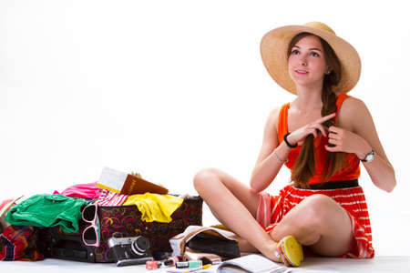 overfilled: Sitting girl near overfilled suitcase. Lady in hat is smiling. Journey brings new impressions. Pile of clothes and cosmetics. Stock Photo