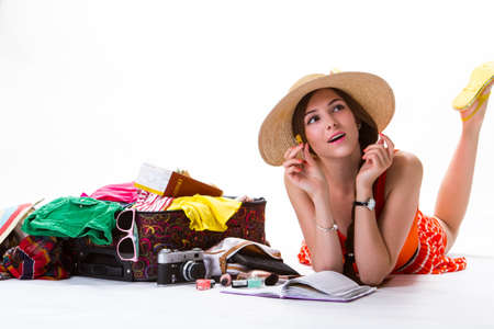 overfilled: Woman lays near overfilled suitcase. Girl with pen and notepad. Write a story about travelling. Remember the funniest things. Stock Photo