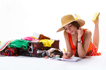 adventurer: Lady lays near overfilled suitcase. Young woman writes in notepad. Letter from an adventurer. Summer trip to sea resort.