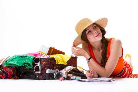 overfilled: Girl lays beside open suitcase. Lady with pen and notepad. Good day for a journey. List of things in luggage. Stock Photo