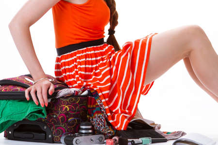 overfilled: Lady sits on overfilled suitcase. Legs of young woman. Baggage for long trip. She took too many things.