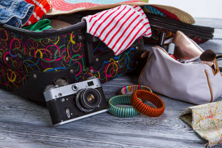 overfilled: Camera near suitcase with clothes. Colorful striped bracelets. Vintage camera on gray shelf. Take some pictures during journey.