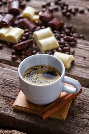 tastes: White cup with coffee. Cinnamon stick and chocolate. Traditional dessert after breakfast. Tastes like pure energy. Stock Photo