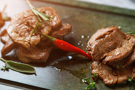 ordered: Meat with herbs and pepper. Red chili pepper and meat. Meat dish ordered at restaurant. Incredibly delicious veal medallions. Stock Photo