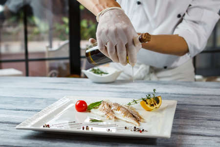 adds: Bottle pours liquid onto fish. Fish with lemon and herbs. Chef adds oil to dish. Delicious dorado fish in restaurant.