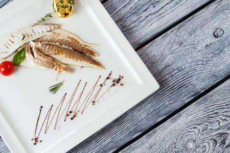 european cuisine: Fish fillet on white plate. Fish with tomato and herbs. Dorado fish and cherry tomato. Beauty of european cuisine. Stock Photo