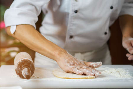 Male hands touching dough. Rolling pin on cooking board. Chefs hand in flour. Precise work of true professional.