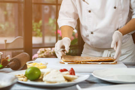 shortcake: Mans hands touch shortcake dough. Thin layers of dough. Chef prepares a cake. Special recipe of tasty dessert.