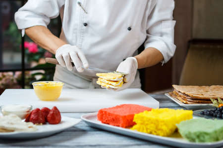 shortcake: Hands putting custard on shortcake. Man prepares dessert at table. Sweet and dense filling. Pastry chef at local restaurant.