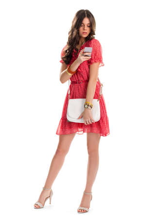 purchased: Lady in dress holds phone. Heel shoes and white bag. Recently purchased smartphone. Its time to call friends.