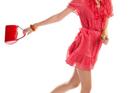 designer bag: Lady in short sleeve dress. Red dress and glossy bag. Model wearing designer clothes. Girls light outfit for summer.