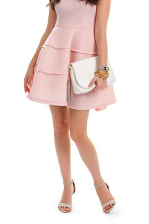 f56149214b  59816372 - Mujer en vestido de salmón. Bolso blanco y zapatos de tacón de  color beige. vestido de cóctel elegante con pliegues.