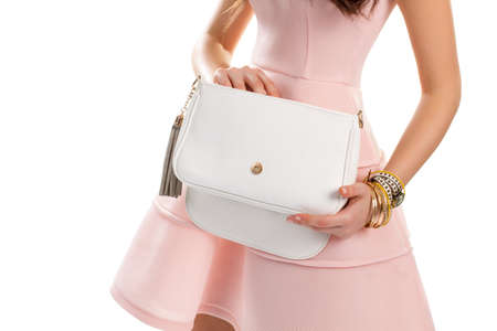 cotton dress: Womans hand holds white bag. Wrist watch and thin bracelets. Cotton dress and leather purse. New salmon dress with bijouterie. Stock Photo